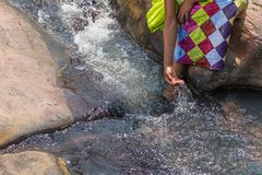 Woman in African outfit on the verge of fluent river. Interactin. G with water. Angola Stock Image