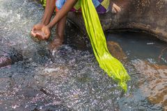 Woman in African outfit on the verge of fluent river. Interactin. G with water. Angola Stock Photography