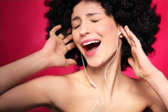 Woman with afro hair enjoying music Royalty Free Stock Image