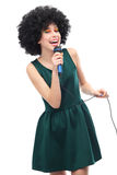 Woman with afro hairstyle doing karaoke. Young woman over white background Royalty Free Stock Photo