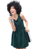 Woman with afro hairstyle holding microphone. Young woman over white background Royalty Free Stock Image