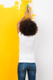 Woman with an afro hairstyle paintinmg a wall Stock Photo