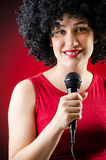 The woman with afro hairstyle singing in karaoke Stock Images