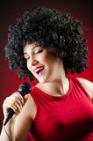 Woman with afro hairstyle singing in karaoke Stock Image