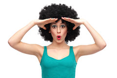 Woman with afro looking into distance. Woman wearing wig over white background Royalty Free Stock Image