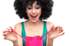Woman with afro looking into shopping bag. Woman wearing wig over white background Royalty Free Stock Photo