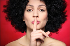 Woman with afro making silence gesture. Young woman over red background Stock Photos