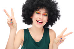 Woman with afro showing peace sign. Woman wearing wig over white background Royalty Free Stock Photo