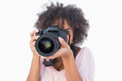 Woman with afro wearing pink top taking a photo. On white background Stock Image