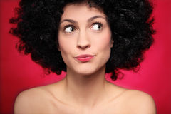Woman with afro wig looking to the side. Young woman over red background Royalty Free Stock Photos