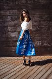Woman against the background of a wooden wall. Beautiful young fashion woman in dress against the background of a wooden wall Stock Photography