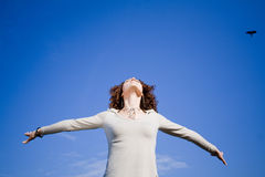 Woman against blue sky. Young woman agains blue sky with arms outstreched Royalty Free Stock Photo