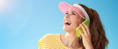 Woman against blue sky looking aside and speaking on cell phone Royalty Free Stock Image