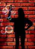 Woman against brick wall Royalty Free Stock Photos