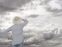 Woman against grey sky. Looking ahead future concept. Royalty Free Stock Images