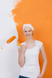Woman against half painted wall Stock Photos