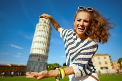 Woman against leaning tower posing for travel photos. Smiling stylish woman in striped blouse posing for travel photos against leaning tower in Pisa, Italy. I royalty free stock photography