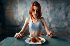 Woman against plate with food, absence of appetite. Unhappy skinny woman against plate with food, absence of appetite. Fat or calories burning concept. Weight Royalty Free Stock Images