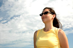 Woman against the sky. Beautiful Puerto Rican woman standing with the sky behind her. Sunglasses on Stock Photos