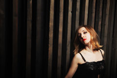 Woman against a wooden wall. Studio portrait of a young passionate woman against a wooden wall royalty free stock photo