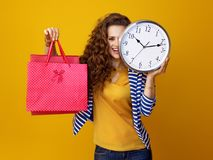 Woman against yellow background with clock and shopping bags. Smiling young woman with long wavy brunette hair against yellow background with clock and shopping stock images
