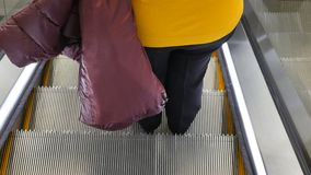 Woman on the escalator at the Mall. Woman in age, look back on her feet standing on the escalator steps stock video