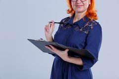 A woman in glasses looks at the tablet with a pen in her hand close-up on a gray background. A woman in age with red hair, in a blue dress, glasses, looks at the Royalty Free Stock Photo