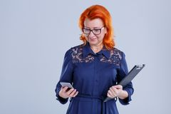 A woman with glasses looks at the phone with a tablet hand on a gray background. A woman in age with red hair, in a blue dress, wearing glasses, looks at the Royalty Free Stock Photography