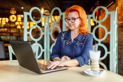 Woman working with a smile behind a laptop at a table on a blurry cafe room. A woman in age, red-haired, in a blue dress and glasses works with a smile behind Royalty Free Stock Photos