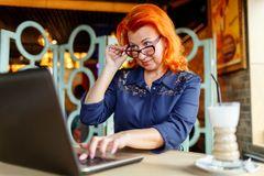 A woman lowering her glasses looks at the laptop at a table in a cafe closeup. A woman in age, red-haired, wearing a blue dress and glasses, having lowered her Stock Photography