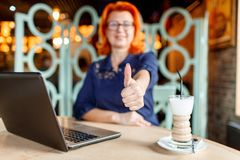 Woman not in focus shows thumb up at table in cafe with laptop. A woman in age, redhead, in a blue dress and glasses is out of focus shows her thumb up at a Royalty Free Stock Images