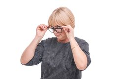 A woman adjusts glasses with both hands and looks to the side on a white isolated background. Woman aged, in gray blouse, blond girl adjusts glasses with both Stock Photos