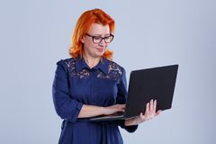 A woman in glasses holds a laptop and works with it on a gray background. A woman, aged with red hair, in a blue dress, with glasses, holds a laptop and works Stock Image