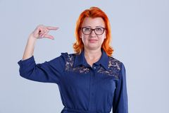 A woman in glasses shows her hand some measure on a gray background. A woman, aged with red hair, in a blue dress, with glasses, shows her hand some measure on a Stock Photo