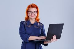 A woman with glasses with a smile holds a laptop and holds her hand on the keyboard on a gray background. A woman, aged with red hair, wearing a blue dress Stock Image