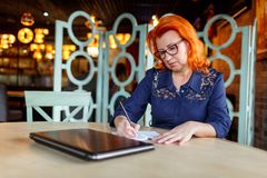 A woman is making notes in a notebook on a desk next to a closed laptop. A woman, aged, red-haired, in a blue dress and glasses, carefully makes notes in a Stock Image