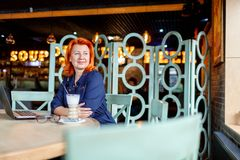 A woman looks away thoughtfully at a table in a cafe with a laptop and a cappuccino. A woman, aged, red-haired, in a blue dress and glasses, looks away Stock Image