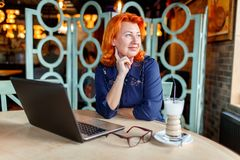 Woman pensively looking away sitting at table with laptop in cafe. Woman aged, red-haired, in blue dress pensively looking away sitting at table with laptop in Stock Image
