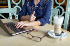Woman working behind laptop at desk in cafe near on blurred background glasses and cappuccino. Woman aged, red-haired, in a blue dress working behind a laptop on Royalty Free Stock Photography