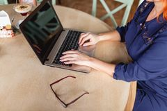 A woman works behind a laptop at a table on which glasses in a cafe close-up. A woman aged, red-haired, in a blue dress is working behind a laptop at a table on Royalty Free Stock Photo