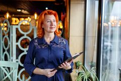 A woman stands thoughtfully with a tablet in her hands at the window in a cafe. A woman, aged, red-haired, in a dark blue dress, aged, red-haired, in a blue Royalty Free Stock Images
