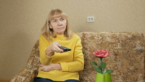 Woman aged switches remote control TV channels on the couch at home. She is resting after a hard day. holiday concept stock footage