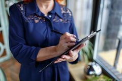 A woman is making notes in a tablet in her hand on a blurred background. Woman aged, wearing a blue dress with a pen, makes notes in a tablet in her hand on a Royalty Free Stock Photography