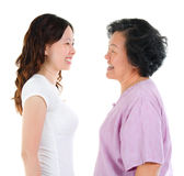 Woman Ageing. Ageing concept. Asian senior mother and adult daughter face to face, profile side view smiling isolated on white background royalty free stock photo