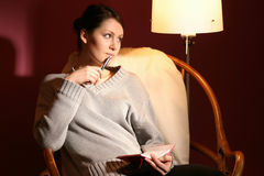 Woman with agenda. Girl, young woman sitting in armchair with agenda on her laps stock photography