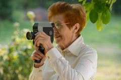 Woman ages shoots a movie camera park. Age eighty years royalty free stock image