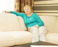 Woman in ages sitting on sofa Royalty Free Stock Photos