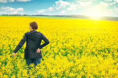 Woman agronomist standing in field of blooming cultivated rapese Stock Photo