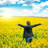 Woman agronomist standing in field of blooming cultivated rapese Royalty Free Stock Photos