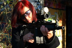Woman aiming assault gun Stock Images